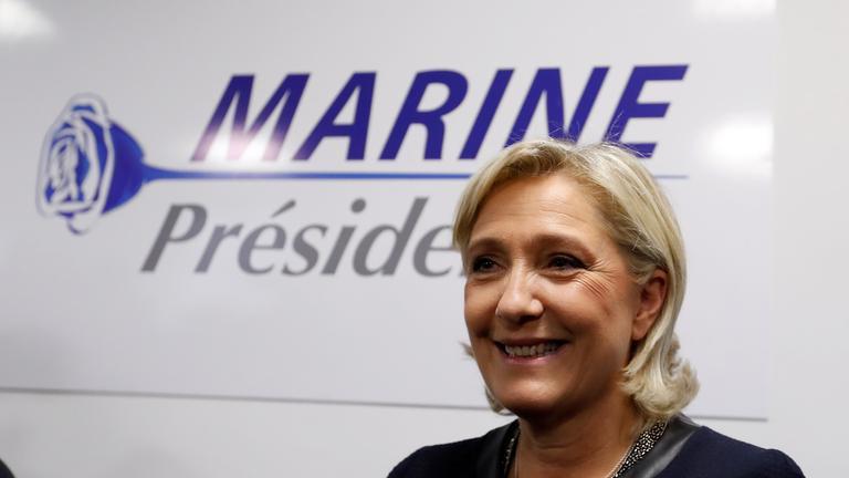 Le Pen lächelnd vor einem Wahlplakat.
