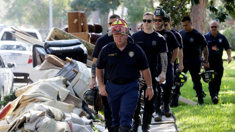 Feuerwehrleute laufen durch die Straßen und räumen auf.
