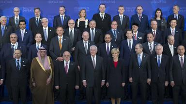 Für das Abschlussfoto der globalen Anti-IS-Koalition stehen die Teilnehmer vor einer blauen Fotowand.