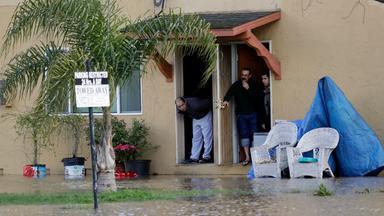 Ein Mann schaut aus der Tür seines Hauses auf die überschwemmte Straße