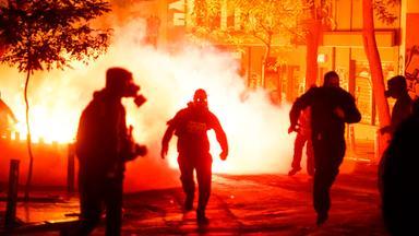Während einer Demo kommt es zu Ausschreitungen. Nebelschwaden und geleißendes Licht erzeugen einen Hintergrund vor dem sich in schwarz vermummte Demonstranten abheben. Das ganze hat eine apokalyptische Stimmung.