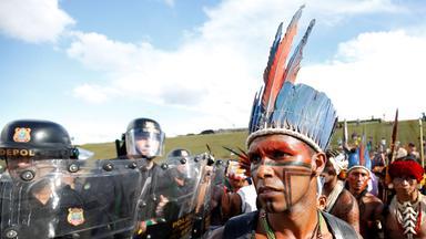 Ein mit Federn und bunter Schminke geschmückter Ureinwohner steht vor einer Wand aus Polizisten