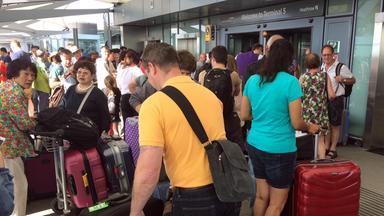 Passagiere in einer langen Schlange an einem Schalter am Flughafen