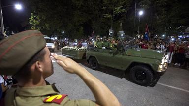 Szene vom Straßenrand beim Trauermarsch mit Fidel Castros Urne, ein Soldat salutiert (im Vordergund).