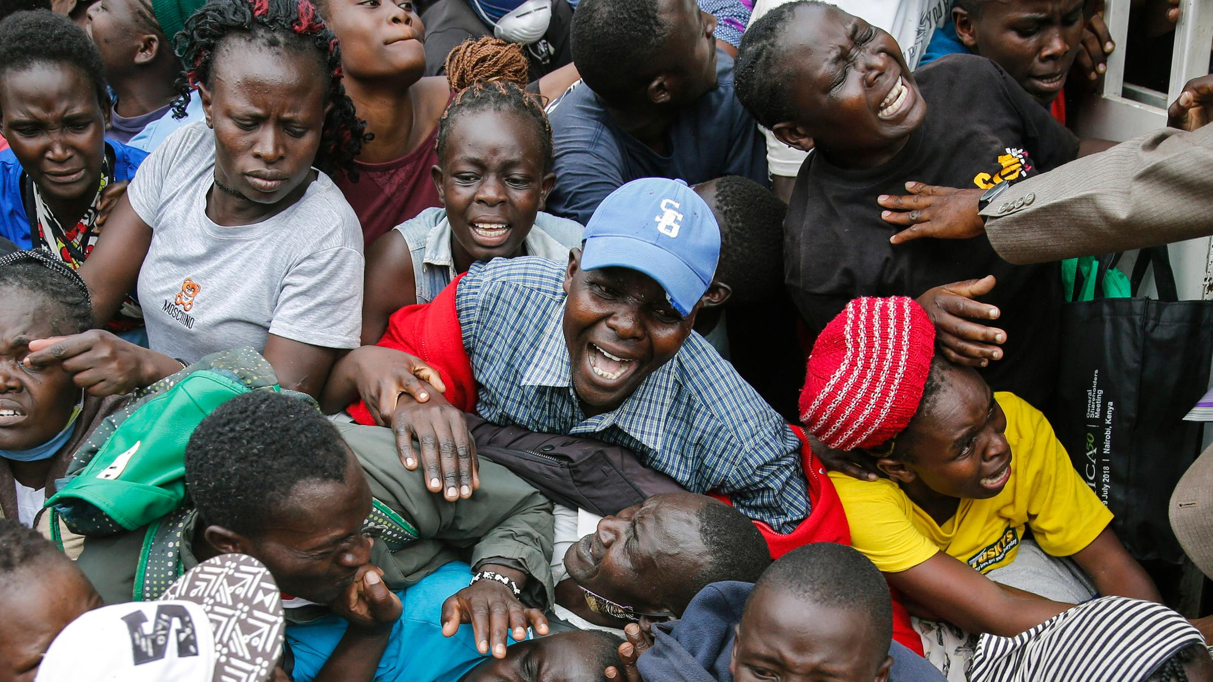 Archiv: Bewohner drängen durch ein Tor, während einer geplanten Verteilung von Nahrungsmitteln, aufgenommen am 10.04.2020 in Kenia, Nairobi.