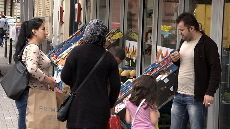 Deutschtürken stehen vor Gemüsegeschäft in Köln