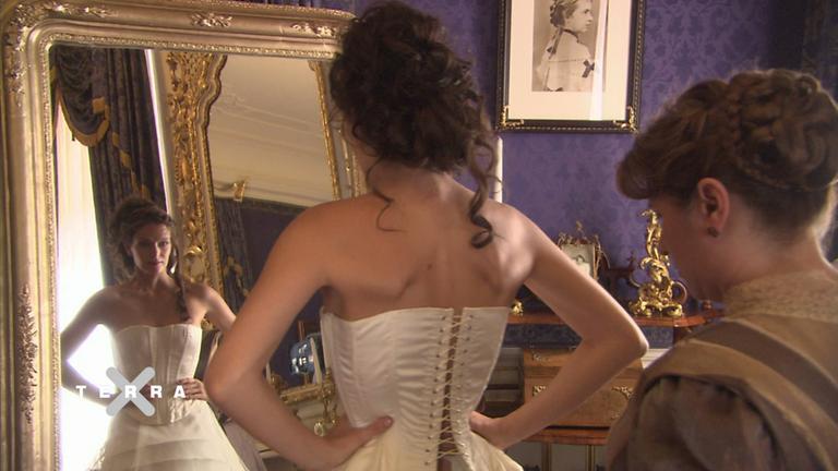 Frau im Korsett vor dem Spiegel
