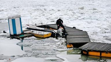 Ein Teilstück der Donau in Osteuropa ist völlig eingefroren. Man sieht ein kleines Boot udn einen Steg, die vom Eis umgeben sind.