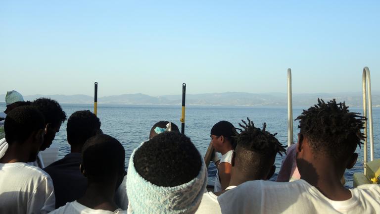 Flüchtlline blicken von einem Boot auf das Mittelmeer.