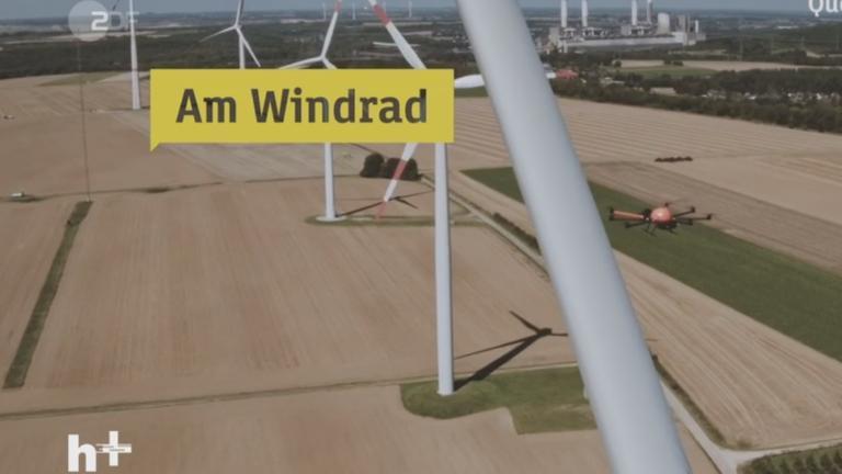 Eine Drohne fliegt zu einer Windkraftanlage