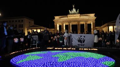 Menschen stehen mit brennenden Kerzen in Form einer Weltkarte vor dem noch beleuchteten Brandenburger Tor.
