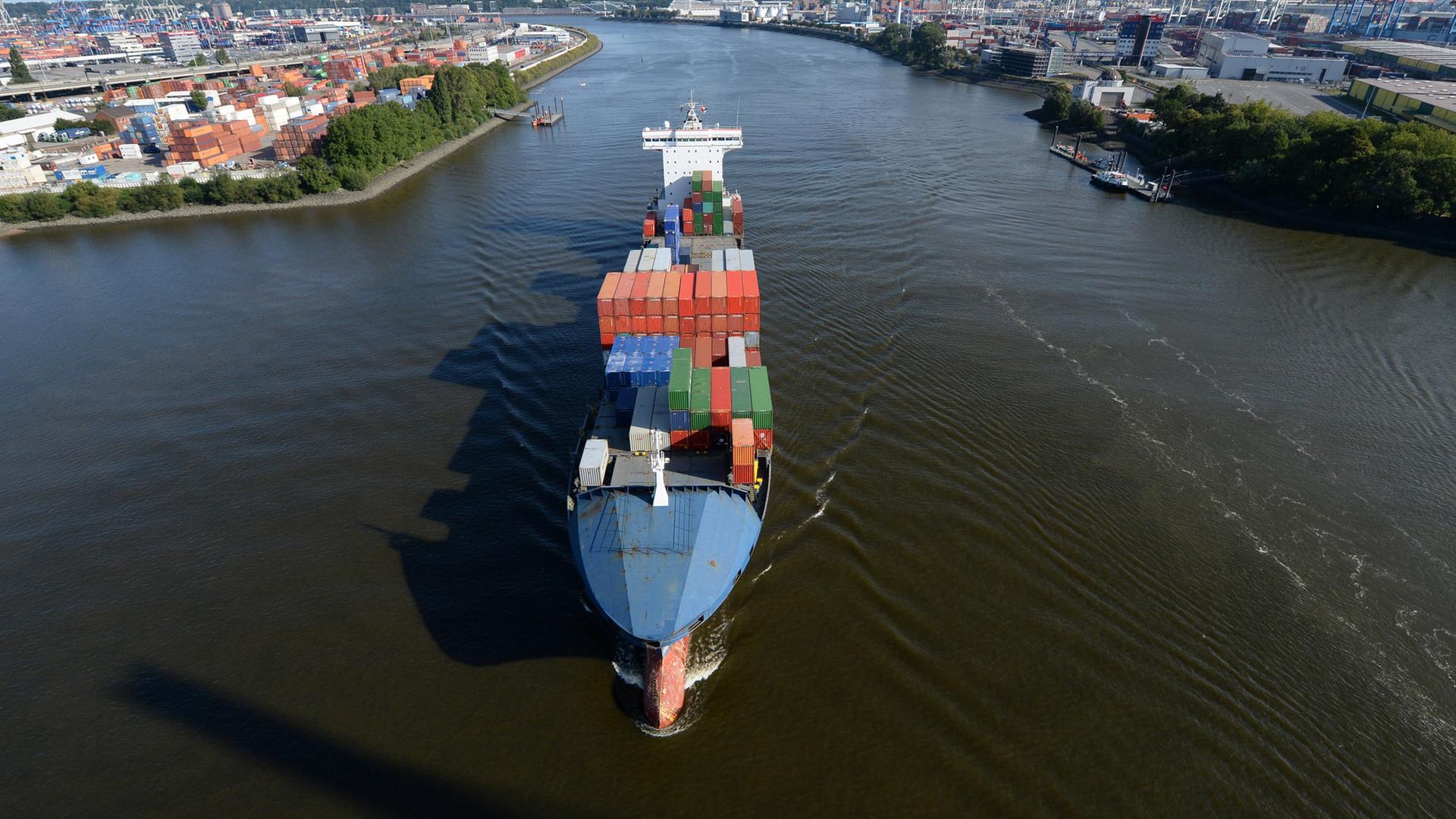 Containerfrachter fährt im Hamburger Hafen auf der Elbe.