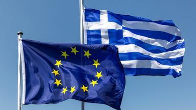 Vor blauem Himmel wehen die europäische und die griechische Flagge.
