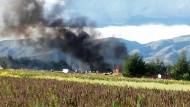 Peru: Flugzeug brennt nach Landung. Zu sehen eine große Rauchwolke auf einem weiten Feld.