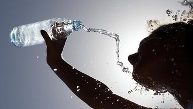 Frau kühlt sich mit Wasser ab