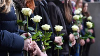 Eine Reihe schwarz gekleideter Besucher, jeweils mit weißer Rose in der Hand.