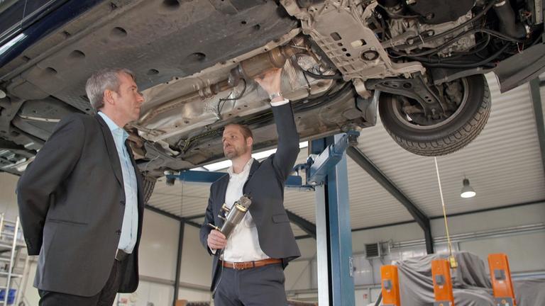 Der Autor mit einem Techniker betrachten die Unterseite eines Autos.
