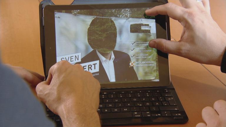 Foto von zerstörtem Wahlplakat von CDU-Politiker auf Bildschirm von Laptop