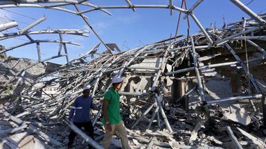 Zwei Männer mit weißen Helmen gehen nach dem Erdbeben durch die Trümmer einer Schule