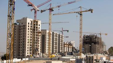 Auf einer Baustelle in Israel stehen mehrere Kräne vor dem Rohbau eines Wohnkomplexes.