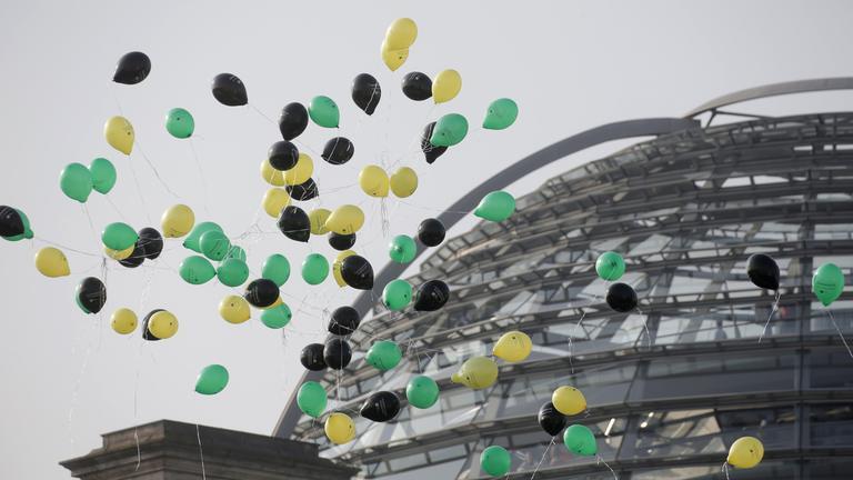 Luftballons in den Farben schwarz, gelb und grün neben der Reichstagskuppel