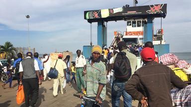 Menschen verlassen eine Fähre in Gambia