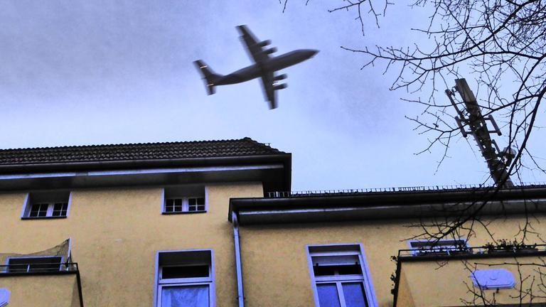 Flugzeug fliegt über Wohngebäude