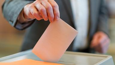 Ein Mann im Anzug steckt einen gefalteten Wahlschein in die Urne.