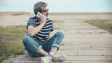 Mann telefoniert am Strand