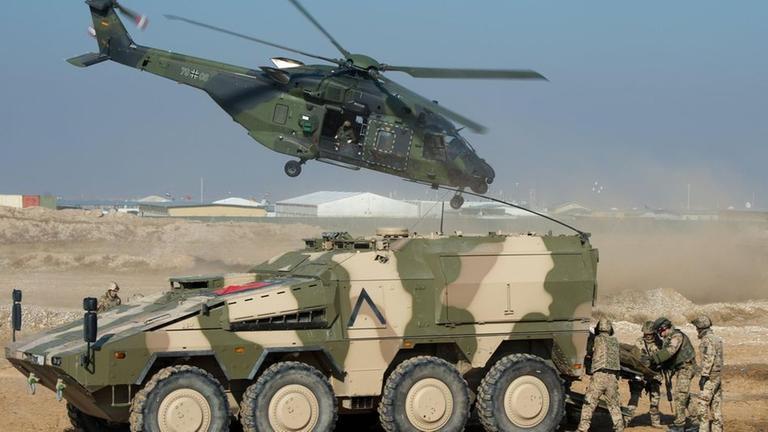 Panzer mit Bodentruppen und ein Militärhubschrauber