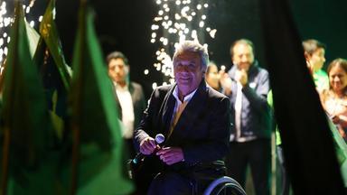 Präsidentschaftskandidat Moreno sitzt im Rollstuhl auf einer Bühne und feiert mit seiner Partei das Wahlergebnis.