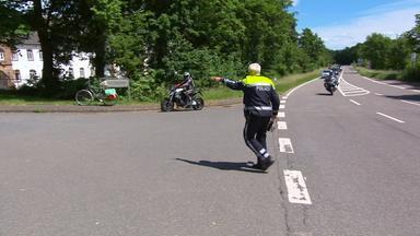 Polizist winkt Motorradfahrer zur Kontrolle aus dem Straßenverkehr