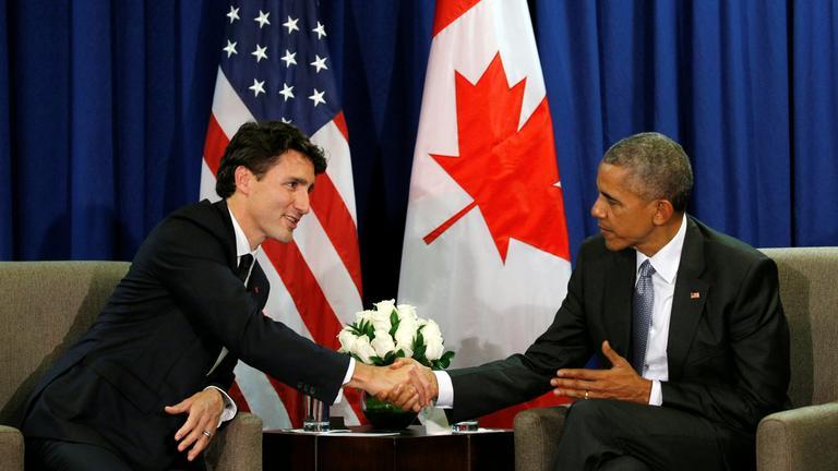 Obama und Trudeau reichen sich die Hand. Beide sitzen in einem Sessel auf einem Podest. Im Hintergrund sind die beiden Fahnen beider Länder zu sehen.