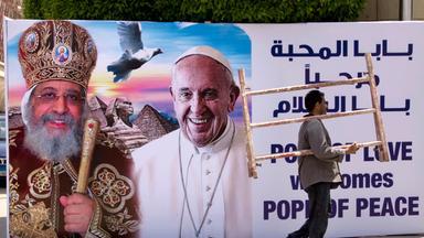 Auf einem Plakat wird Papst Franziskus willkommen geheißen neben ihm ist der koptische Papst Tawadros II zu sehen.