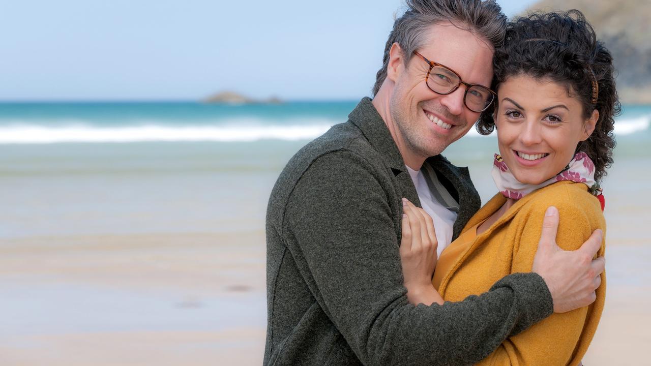 """""""Rosamunde Pilcher: Wie von einem anderen Stern"""": Natalie (Liza Tzschirner) und Benjamin (Daniel Aichinger) stehen sich Arm in Arm am Strand gegenüber und lächeln in die Kamera."""