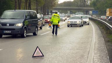 Polizist stellt nach Unfall Warnlampen auf Fahrbahn der A1