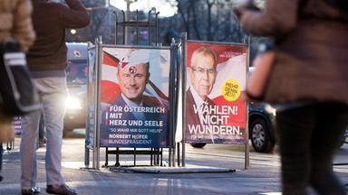 Wahlplakate von Hofer und Van der Bellen auf einer Straße. Das von Hofer ist leicht beschädigt und mit einem Sticker verziert worden.