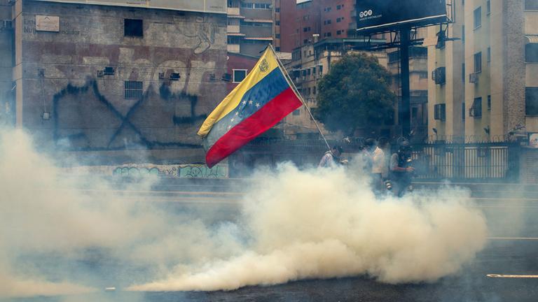 Demonstranten stehen mit Masken in einer Tränengaswolke in Caracas, Venezuela, und halten die venezolanische Flagge.