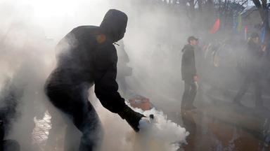 Ein Aktivist wirft am Rande einer Demonstration in Kiew eine Rauchgranate in Richtung der Polizei.