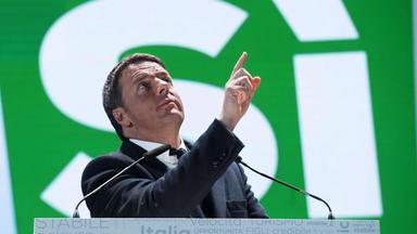 """Renzi an einem Rednerpult, deutet mit dem Finger gen Himmel. Hinter ihm ein grünes Plakat mit der weißen Aufschrift """"Si""""."""