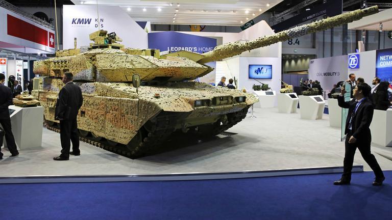 Auf der Internationalen Ausstellung für Verteidigung in Abu Dhabi gehen Menschen an einem ausgestellten Panzer vorbei.