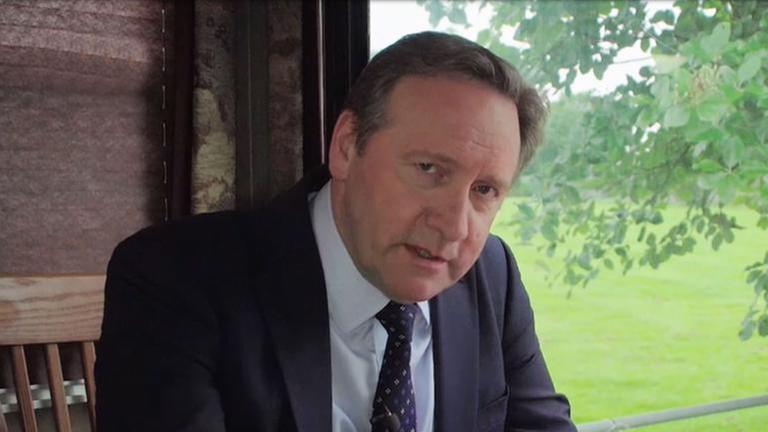 Schauspieler Neil Dudgeon sitzt an einem Tisch