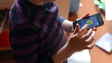 Kind spielt mit Smartphone.