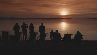 Menschen stehen am Ufer bei Sonnenuntergang am Chiemsee