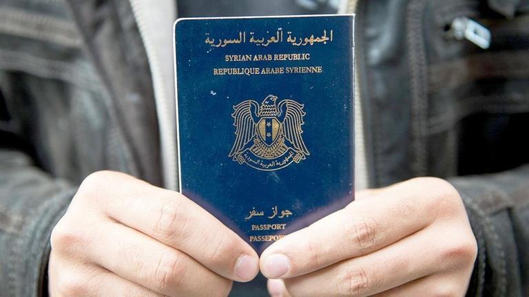 Archiv - Ein Mann hält am 08.09.2015 auf dem Hauptbahnhof in Lübeck, Schleswig-Holstein, einen syrischen Pass in die Kamera
