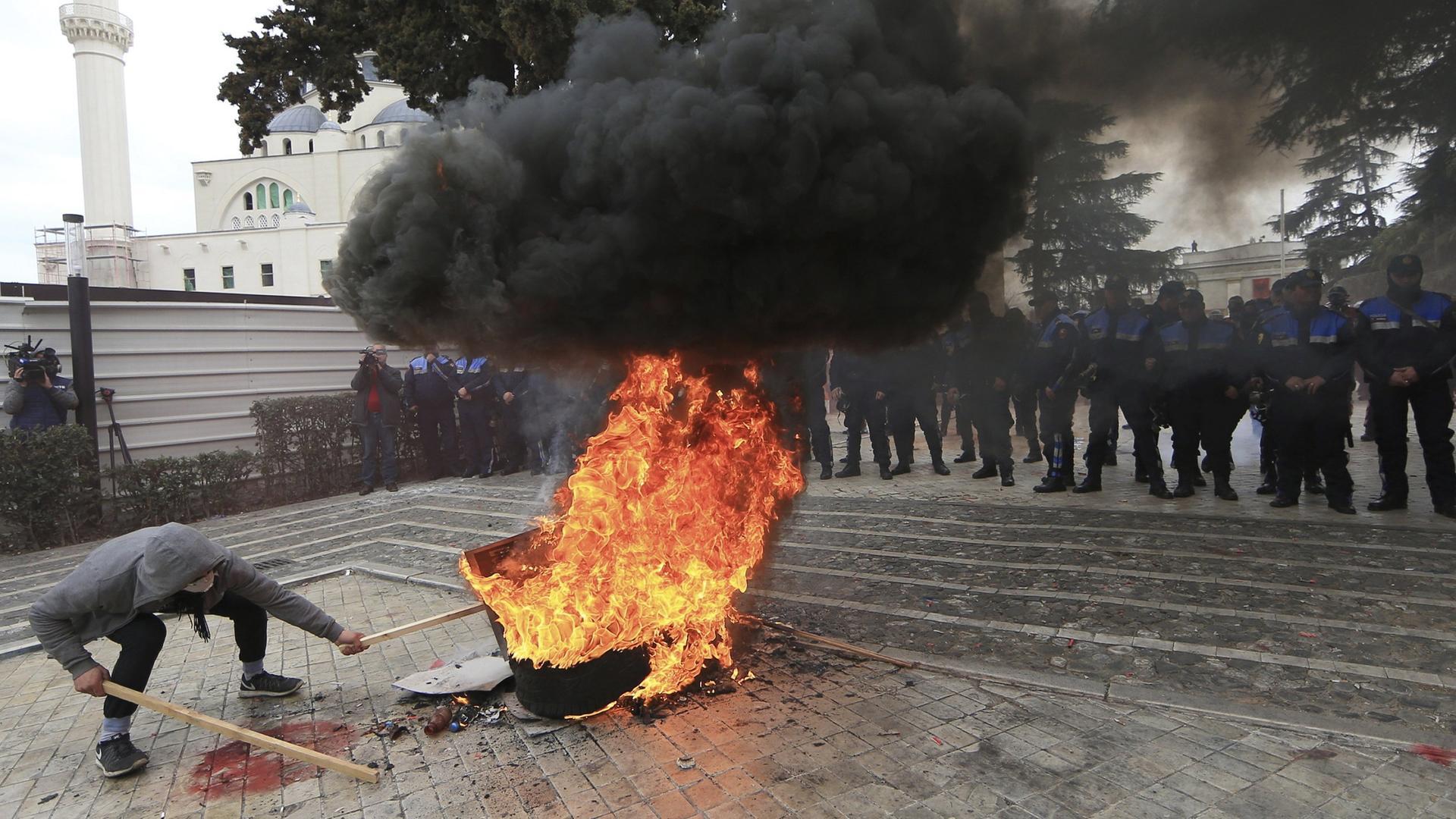Ein Demonstrant verbrennt Reifen vor dem Parlamentsgebäude.