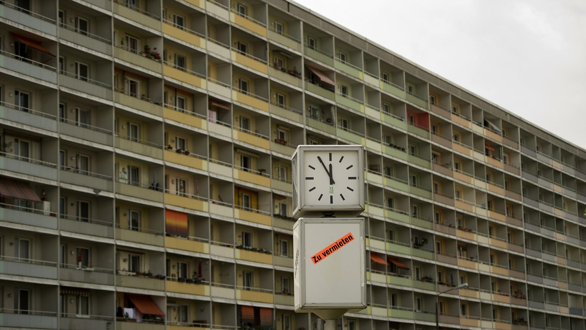 Uhr vor DDR-Plattenbau zeigt «Fünf vor Zwölf» an. Archivbild