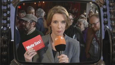 """ZDF-Reporterin hält Karte mit Aufschrift """"Mehr Sex"""""""