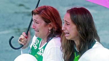 Trauerszene im Stdaion von Chapeco. Zwei bitterlich weinende Frauen unter einem Regenschirm.