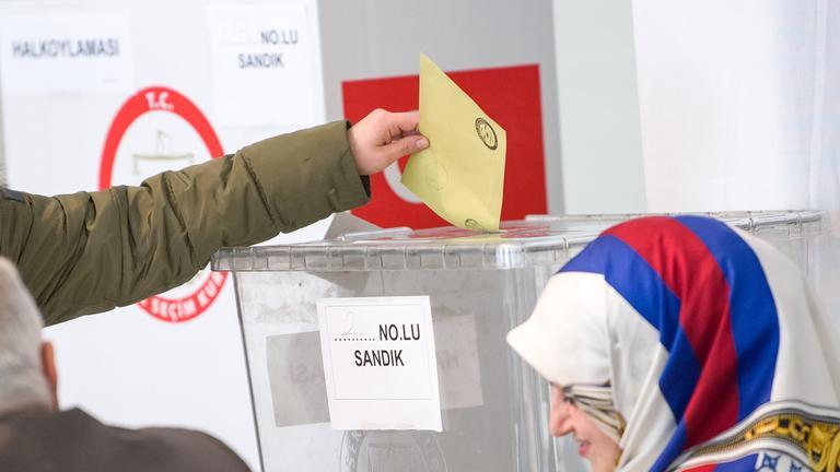 Eine Wahlhelferin sitzt am 27.03.2017 in München in einem Wahllokal, während ein Mann seine Stimme abgibt
